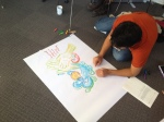 Student working on poster on the floor